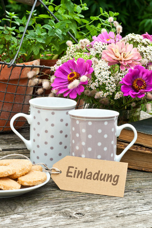 coffee hour: two coffee mugs old books, flowers and label with lettering invitation