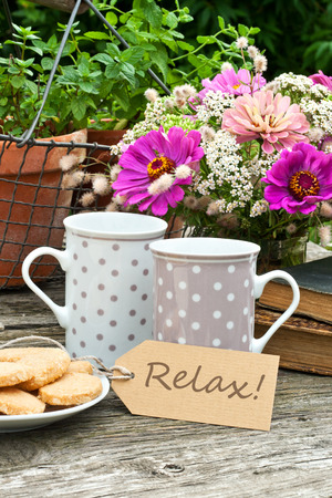 coffee hour: two coffee mugs old books, flowers and label with lettering relax Stock Photo