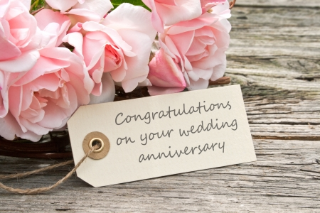 felicitaciones: rosas de color rosa y una tarjeta de aniversario de bodas