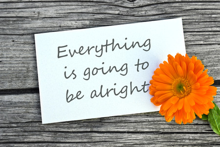 alright: orange marigold and white card with lettering  everything is going to be alright Stock Photo