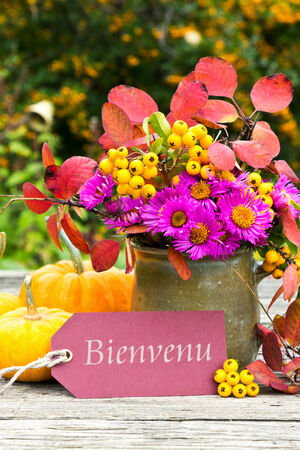 Flowers, pumpkins and card with lettering welcome photo