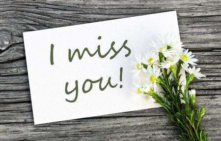 te extra�o: Tarjeta blanca con flores de color blanco y las letras que te echo de menos