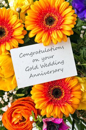 aniversario de boda: ramo con gerberas y la tarjeta de oro del aniversario de boda Foto de archivo