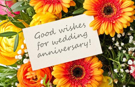 aniversario de boda: ramo con gerberas y la tarjeta de aniversario de boda Foto de archivo