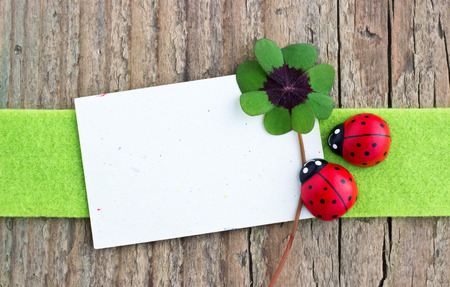 Leafed clover, ladybugs and card on wooden board