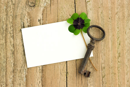 White card with key and clover  on  board