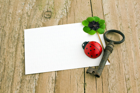 White card with key, ladybugs and clover  on  board