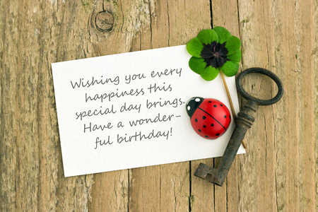 Birthday card with leafed clover, key and ladybugs