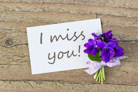 te extra�o: Ramo de violetas y tarjeta con las letras que te echo de menos Foto de archivo