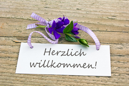 warmest: Bunch of violet flowers and card with lettering warmest welcome
