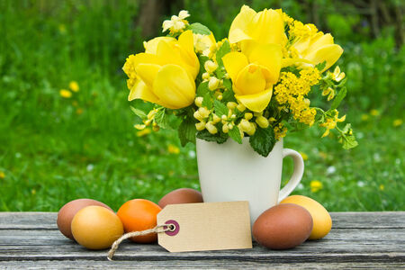 Bouquet with yellow tulips, easter eggs and label photo
