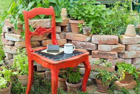 rode stoel in een tuin met kruiden, beker en boeken Stockfoto