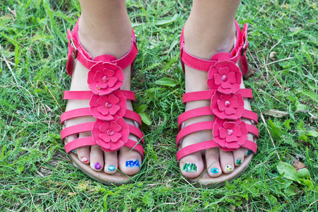 children s feet in red sandals and painted toenails