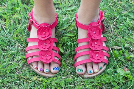 uñas pintadas: pies de los niños s en sandalias rojas y uñas de los pies pintadas Foto de archivo