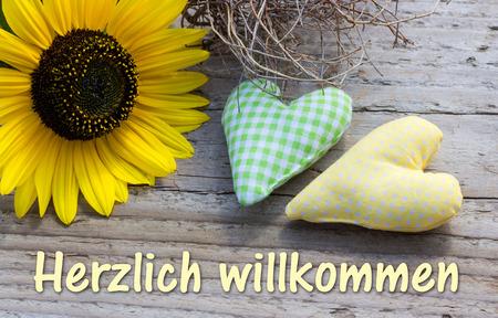 Sonnenblume mit zwei Herzen und Schriftzug willkommen Standard-Bild