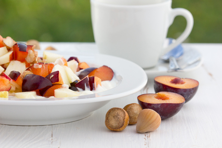 fruit salad with fresh plums, apples and hazelnuts photo