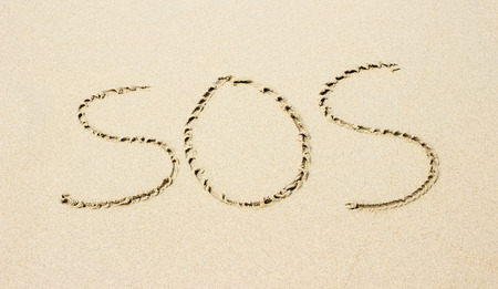 sos: sand with lettering SOS