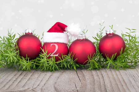 Four red christmas balls with christmas hat Standard-Bild