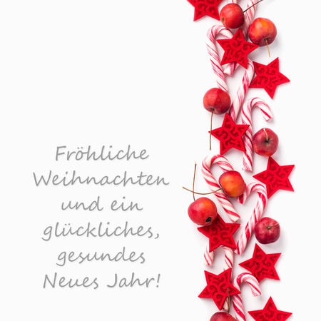 German Christmas card with candy canes, apples and text Merry Christmas and a happy New Year Standard-Bild