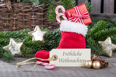 german christmas card with red sock, gifts, Candy canes and text merry christmas photo