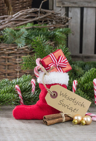 Polish christmas card with red sock, gifts, Candy canes and text merry christmas photo