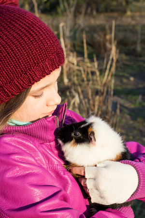 A girl holding a guinea pig on the arm photo