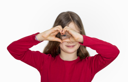 cordiality: A girl with long hair shows with hands a heart Stock Photo