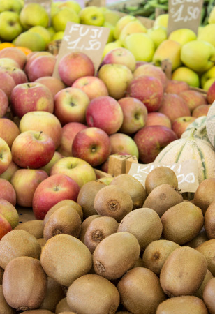 kiwis: Display with lots of fresh kiwis and apples Stock Photo