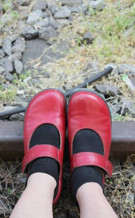 red shoes: Feet with red shoes on railway tracks Stock Photo
