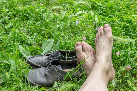 black shoes: Feet and dusty, black shoes in the grass