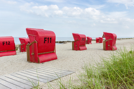 groyne: Baltic Sea beach with red beach chairs and blue sky