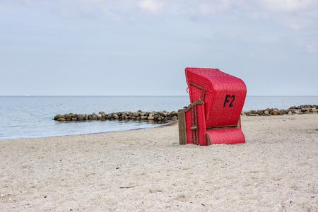 groyne: A red beach chair standing on the sandy beach