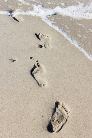 run way: Footprints in wet beach sand Stock Photo