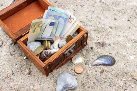 billets euros: Wooden box with euro notes and coins in the sand Banque d'images
