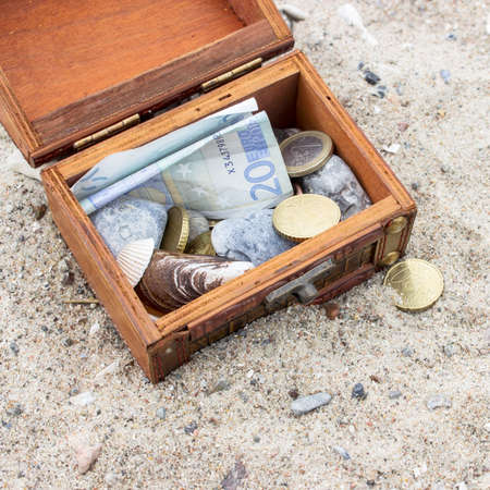 treasure chest: Wooden box with euro notes and coins in the sand Foto de archivo