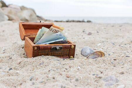 billets euros: Boîte en bois avec des notes et pièces en euros dans le sable