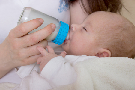 feeding bottle: Newborn baby in the arms of his mother drinking from the feeding bottle