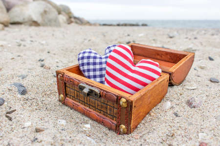 treasure chest: Wooden box with two hearts on the sandy beach