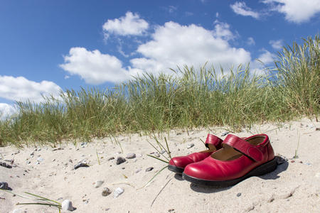 baltic sea: Red shoes on a sandy beach on the Baltic Sea