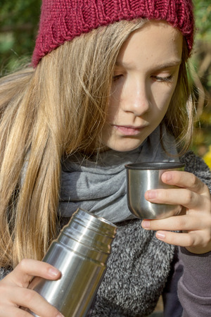thermos: Girl drinks tea from a thermos