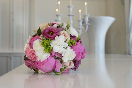 Bridal bouquet with pink and white flowers and candles in the background Stock Photo