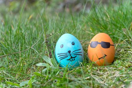 azul y naranja huevo de Pascua con las caras divertidas en la hierba