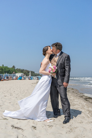 a newly married couple kissing eachother on the Baltic beach