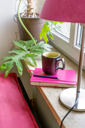 Pink notebook, pen and cup on the window sill