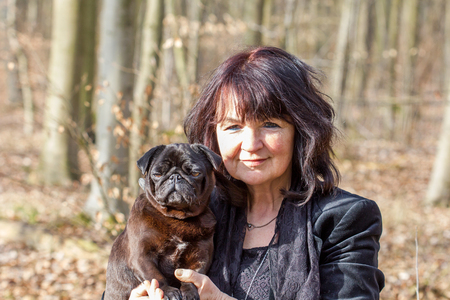 A woman and a black pug in the forest
