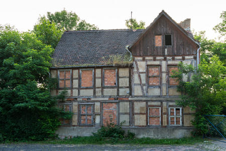 Facade of an uninhabited, decayed half-timbered house