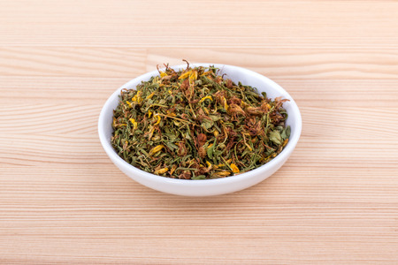 Bowl of dried St. Johns wort on wooden background