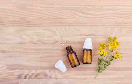 Top view of a homeopathic medicine with blooming St. Johns word on a wooden background with copy space