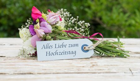 Bouquet with fragrant vetches and card with German text: All the love for the wedding day Standard-Bild