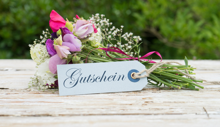 Bouquet with fragrant vetches and greeting card with german text: gift card Stock Photo